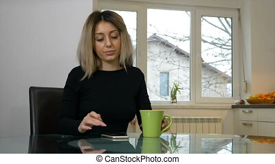 Woman sitting in the kitchen and scrolling the phone while drinking coffee