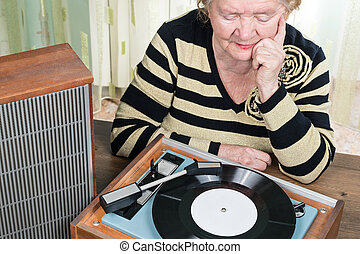 Old woman listening to music from turntable - The elderly...
