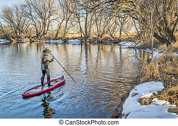 Stand up paddler poling on shallow river - Cache la Poudre...