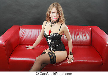 Woman wearing lingerie sitting on sofa with pepper - Sensual...