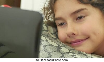 girl playing in a laptop lying on the bed, online games -...