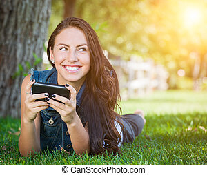 Mixed Race Young Female Texting on Cell Phone Outside In The Grass