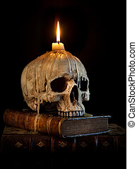 Candle on skull 2 - Halloween image with a burning candle on...