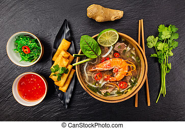 Asian soup pho bo with spring rolls, top view, served on...