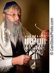 Lighting the menorah - Old jewish man with beard lighting...
