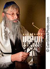 Lighting the menorah - Old jewish man with beard lighting...