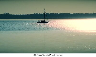 Sail boat silhouette far off on a lake or river at dusk