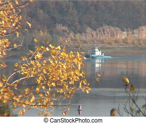 autumn landscape with a view of the river with a tugboat...