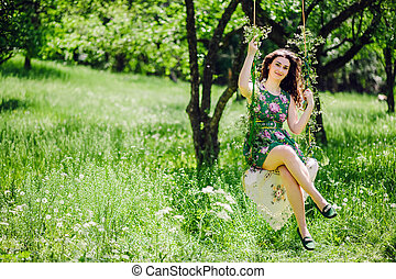 woman ride on a swing. Green park.