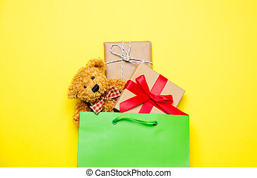 cute gifts in beautiful green shopping bag and teddy bear on...