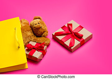 cute gifts, teddy bear and cool yellow shopping bag on the...