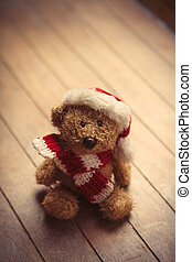 cute teddy bear in santa claus hat on the wonderful brown...