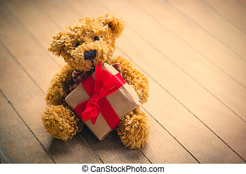 cute teddy bear holding beautiful small gift on the...