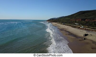 4k aerial clip tilting up over a beach in Malibu,...