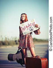 Beautiful young hippie girl hitchhiking on a road -...