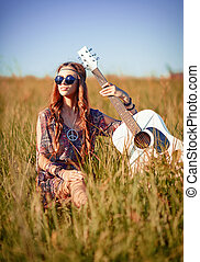 Portrait of lovely young hippie girl with guitar. Shot in...