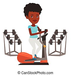 Woman exercising on elliptical trainer. - African woman...