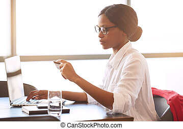 Side view of attractive young black woman doing online shopping