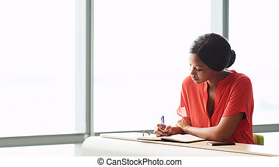 Female African writer busy working while seated next to a...