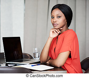 Attractive young black businesswoman sitting at her desk...