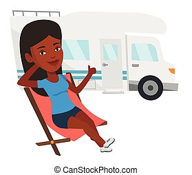 Woman sitting in chair in front of camper van. - African...