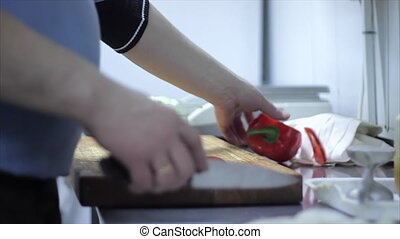 chef hands slicing sweet Red Bell Pepper on a wooden cutting...