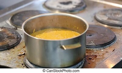 sauce being cooked in a pan - orange thick sauce being...