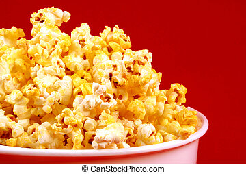 Buttered Popcorn, with Red Background - A white bowl of...