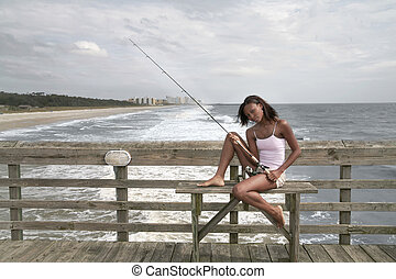 woman fishing on the pier - African American twenties woman...