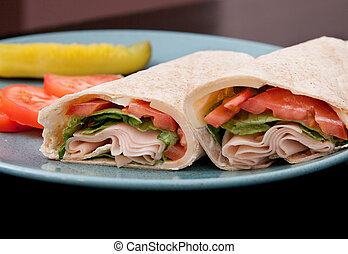 turkey wraps - one sliced turkey wrap on a blue plate with...