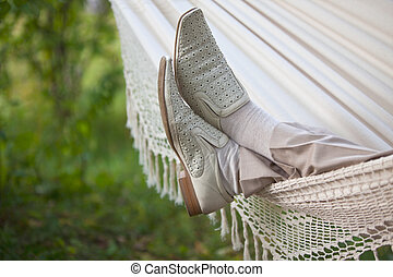 man in light suit in fabric hammock - man's legs in light...
