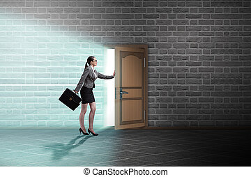 Businesswoman walking towards open door