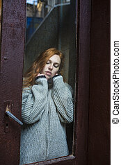 Sensual redhead model behind the glass door