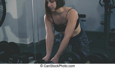 Pretty girl working out in the gym using dumb-bells for...