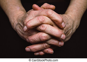 Old hands clasped together - Old hands of senior clasped...