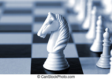 White Knight - White knight on a chess board. Shallow depth...