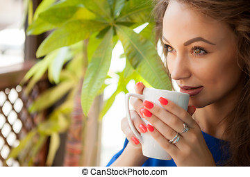 Gorgeous young woman drinking coffe in a coffee shop