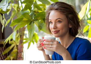 Beautiful young woman drinking coffe in a coffee shop