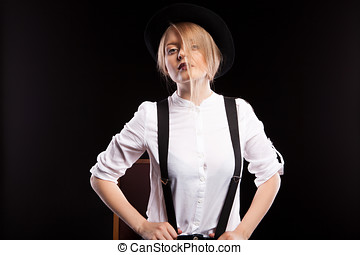 Fashion model in a hat on black background