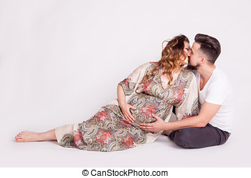Kissing couple with pregnant woman in studio photo