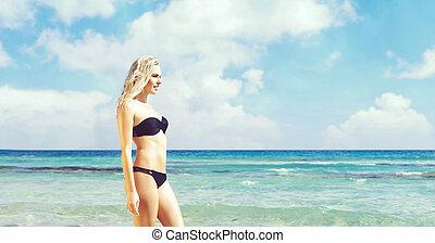 Beautiful and attractive woman in black bikini. Young girl...