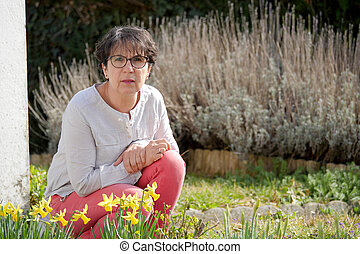 brunette mature woman in her garden with daffodils -...