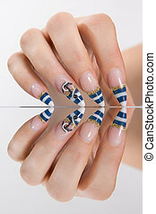 Marine style manicure - Female hand with a marine style...