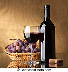 A bottle of red wine, glass and grapes on a golden...