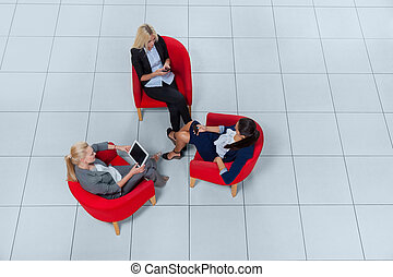 Business Woman Group Sitting In Armchairs Using Gadgets...