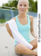 Smiling athletic runner sitting on the ground and takes a...