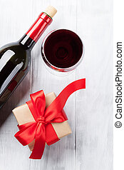 Red wine and gift box on wooden table. Top view