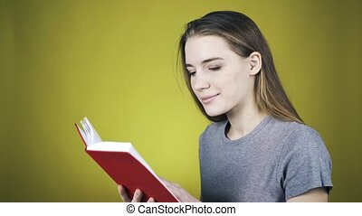 Young pretty woman is reading a red book over yellow...