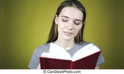 Young beautiful woman is reading a red book over yellow...