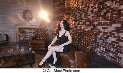 Sexy brunette in an evening dress on a leather couch.Slow...